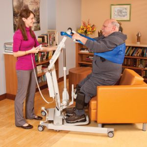 medical assistant transferring patient safely with a sit to stand lift