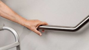 Close-up of hand on grab bar and a walker