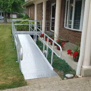 Modular aluminum ramp with one person helping another person in a wheelchair
