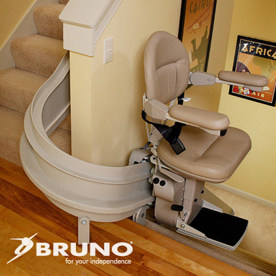 Curved stair lift with beige seat on carpeted staircase with wood floor landing