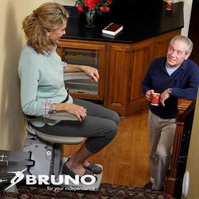 Woman seated in chair of a stairlift talking with her husband