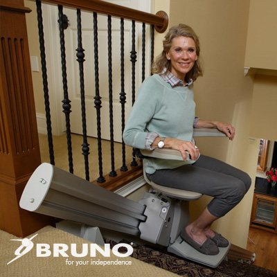 Woman sitting in the chair of a stairlift near the top of a staircase